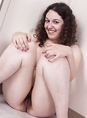 Sweet hairy girl Tamar strips off her purple dress, playing with her hairy pussy while she sits naked on her kitchen floor. She spreads her legs and s